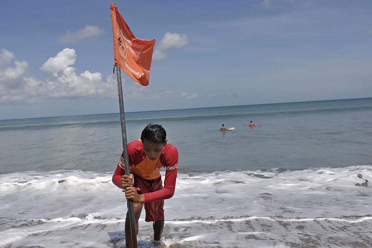 Petugas Badan Penyelamat Wisata Tirtha (Balawista) Kabupaten Badung memasang bendera rambu-rambu larangan berenang menyusul adanya seruan kewaspadaan dampak Tsunami Chili, di Pantai Kuta, Bali, Kamis (3/4). Badan Penanggulangan Bencana Daerah sebelumnya telah mengeluarkan himbauan bagi masyarakat dan wisatawan untuk menjauhi pantai namun aktifitas wisatawan masih tetap berjalan normal. ANTARA FOTO/Nyoman Budhiana/ss/Spt/14.